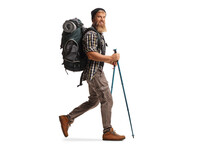 Full Length Profile Shot Of A Bearded Guy Hiker With A Backpack And Hiking Poles Walking