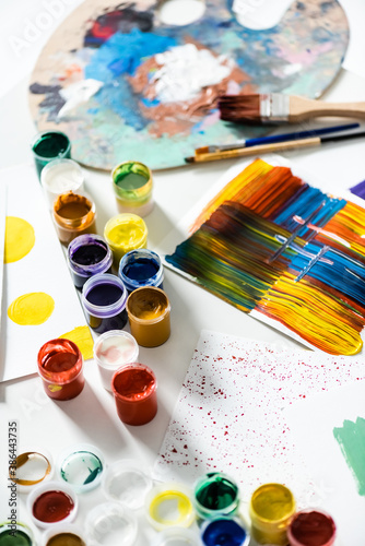 gouache paints, paintbrushes and abstract colorful brushstrokes on paper on whit Canvas Print
