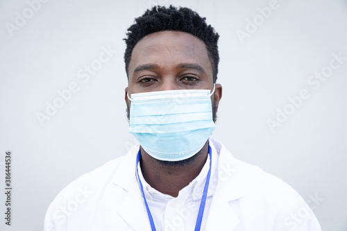 Portrait of male health professional wearing face mask against grey background