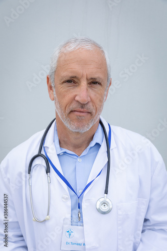 Portrait of senior male doctor against grey background