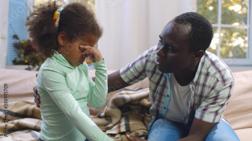 Leinwand Poster Supportive black dad talking and cheering sad toddler daughter