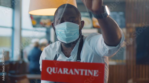 Fotografía Afro-american waiter wearing safety mask hanging quarantine sign in glass door o