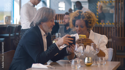 Papel de parede Portrait of diverse business partners on lunch in cafe using smartphone and talk