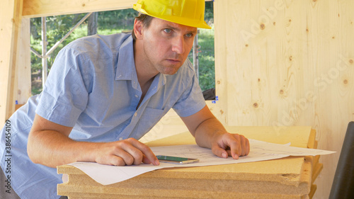 Papel de parede CLOSE UP: Worried carpenter looks around the room while analyzing the blueprints