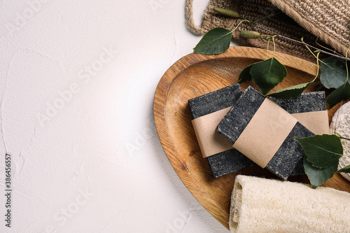 Flat lay composition with natural tar soap on white table, space for text