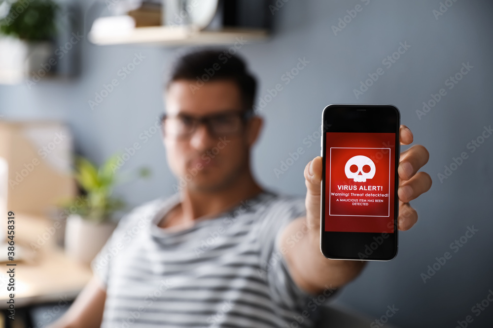 Fototapeta Man holding smartphone with warning about virus attack at home, focus on hand