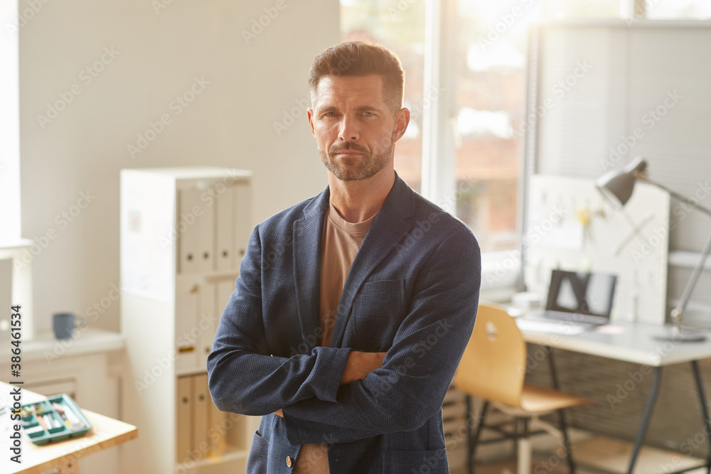Fototapeta Waist up portrait of handsome mature businessman looking at camera while standing with arms crossed in office lit by sunlight, copy space