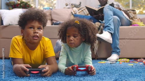 Fototapeta Portrait of cute african preteen brother and sister lying on carpet playing vide