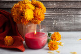 Lit aroma red candle and orange flowers