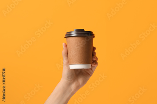 Obraz Woman holding takeaway paper coffee cup on orange background, closeup - fototapety do salonu