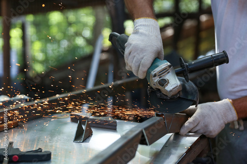 Fotografie, Tablou a worker cuts metal with a grinder close up
