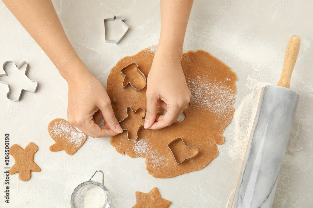 Fototapeta Woman making Christmas cookies at light table, top view