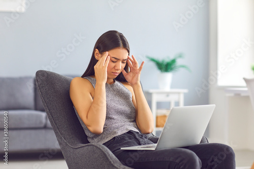 Fotografía Tired young woman rubbing temples suffering from headache sitting in armchair wi