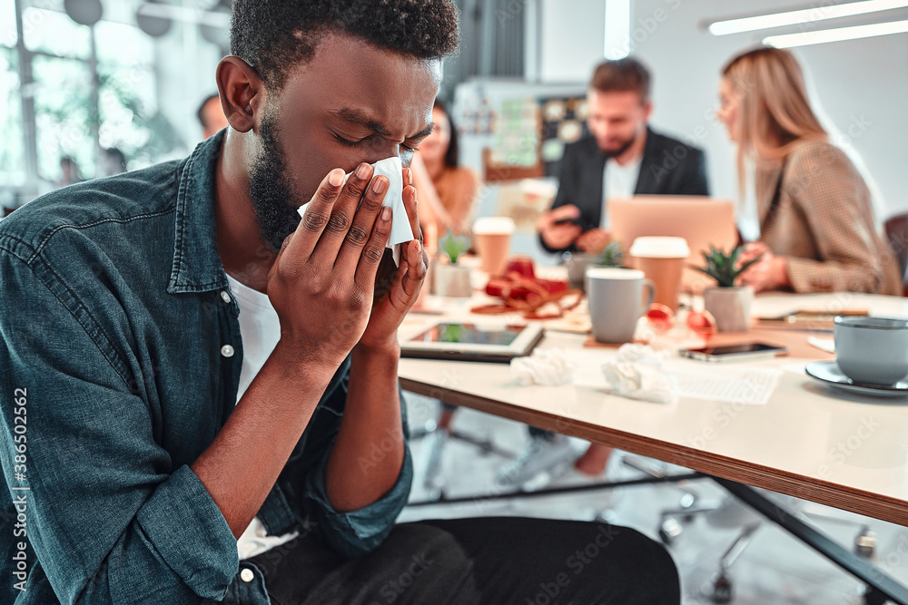 Fototapeta Portrait of ill, sick bearded african male sneezes and coughs, uses handkerchief, rubs nose. Man has running nose, caugh, bad cold, sits at work place