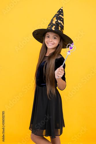 Fotografia, Obraz happy kid wear witch hat holding magic wand to create enchantment on halloween,