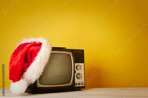 retro television with christmas hat on yellow background © xavier gallego morel