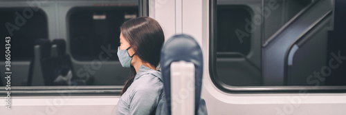 Fototapeta Train commute mandatory face mask wearing for coronavirus pandemic. Panoramic banner of people lifestyle commuting after work at night banner. Travel woman passenger wearing cover. obraz