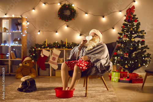Obraz Santa relaxing at home after long day of work, enjoying cup of tea and soaking feet in warm water - fototapety do salonu