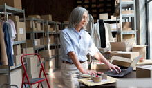 Older Middle Aged Business Woman Entrepreneur, Fashion Clothing Seller Using Laptop Checking Ecommerce Dropshipping Order Packing Online Shop Shipping Delivery Parcels Boxes At Workplace In Warehouse.