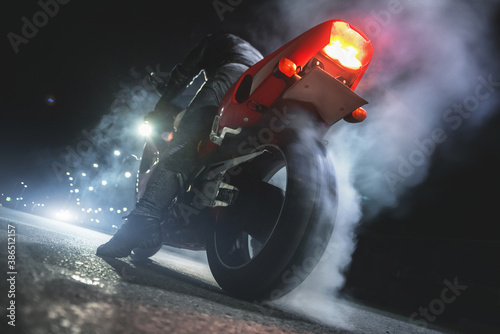 Obraz Motorbiker is burning a tire rubber on night road. - fototapety do salonu