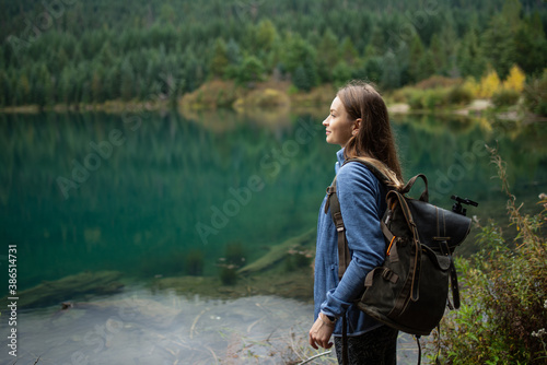 Obraz Young beautiful woman standing near amazing lake with clean blue water on wooded mountains background. Concept of friendly with nature. Close-up side view. Enjoyment of clear air. Relaxation. - fototapety do salonu