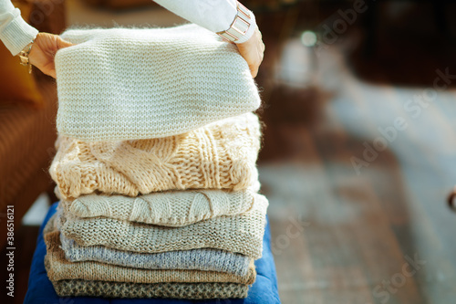 Obraz Closeup on elegant woman prepare sweaters pile for storage - fototapety do salonu