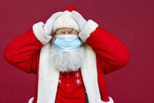Tired Old Bearded Ill Santa Claus In Panic Wearing Costume, Face Mask Feeling Headache, Stress, Getting Sick On Christmas Holidays Standing On Red Background. Covid 19 Coronavirus Problem Concept.
