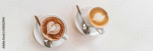 Fotografering Two coffee cups top view on white table banner background