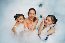 Asian Women Friends Enjoy Playing Together In Foam Bobbles Pool Party