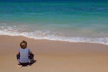 Boy Crouching On The Beach, Fa...