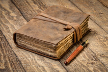 Antique Leatherbound Journal With Decked Edge Handmade Paper Pages And A Stylish Pen On A Rustic Wooden Table, Journaling Concept