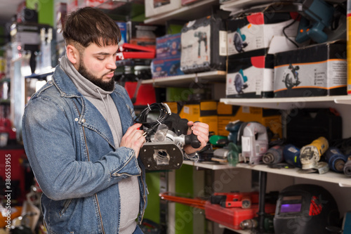 Photo Attentive man chooses wood router in a tool store