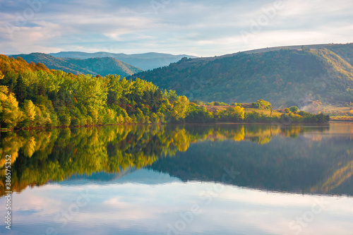 Obraz gilau lake of cluj country in evening light. beautiful landscape of romania in autumn. reflection on the calm water surface. trees in colorful foliage. sunny weather - fototapety do salonu