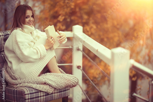 girl in a knitted sweater reads a book on the veranda in the park, seasonal roma Canvas Print