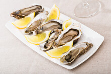 Tasty Oysters With Lemon On Plate Top View. High Quality Photo