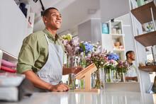 Merry Young Man Enjoying Work At Florist