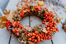 Close Up Photo Of Handmade Colorful Floral Autumn Door Wreath Made Of Colorful Rosehip Berries, Rowan, Dry Flowers And Oak Leaves. Fall Flower Decoration Workshop.