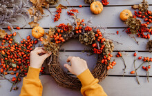 Girl Making Floral Autumn Door Wreath Using Colorful Rosehip Berries, Rowan, Dry Flowers And Pumpkins. Fall Flower Decoration Workshop, Florist At Work.