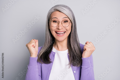 Fotomural Photo of funny lovely retired lady raise up fists excited surprised triumphant b