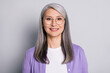 Portrait photo of positive smiling elder woman wearing eyeglasses and purple cardigan isolated on grey color background