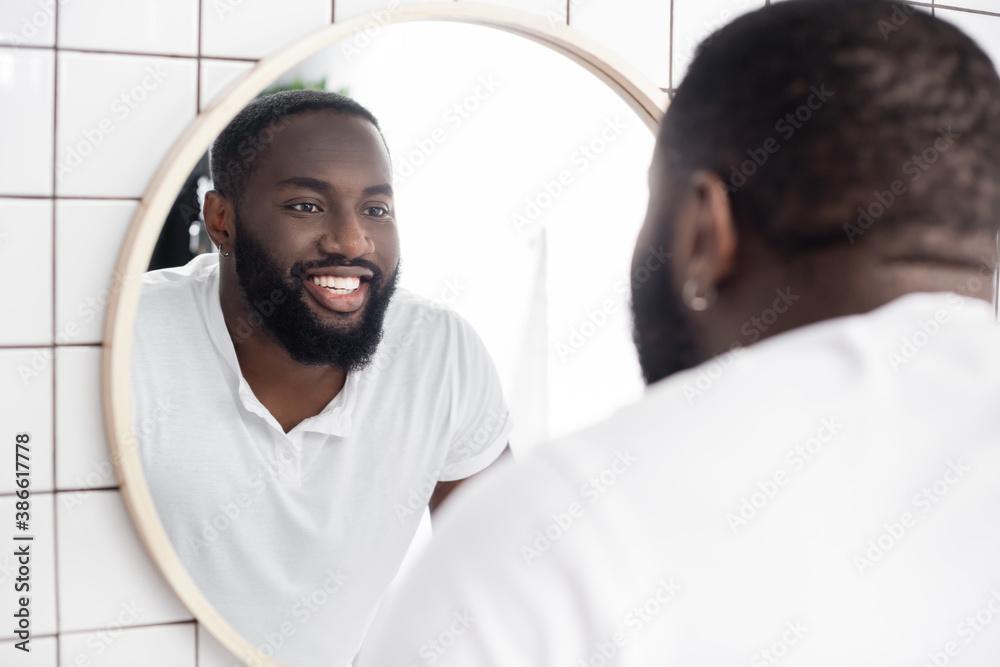 Fototapeta smiling afro-american man looking in mirror