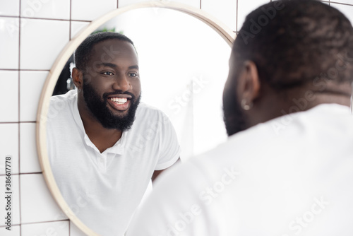 smiling afro-american man looking in mirror - 386617778