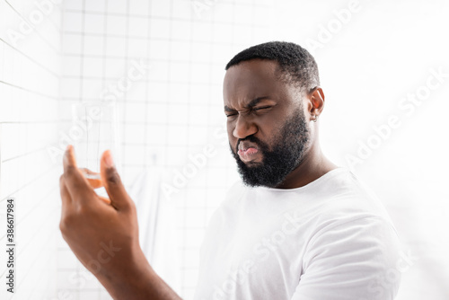 Obraz afro-american man grimacing from bad taste of water and holding glass in hand - fototapety do salonu