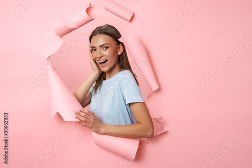 Vászonkép Young woman in t-shirt smiling and posing isolated over pink background