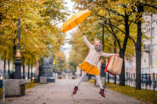 Fotografija Happy girl in a jump on the autumn city street with bright yellow umbrella and shopping bags