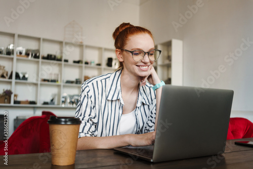 Young woman using laptop for webinar - 386623520