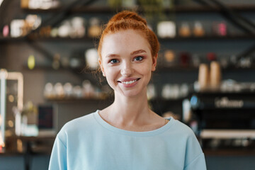 Smiling young woman standing at the coffee shop