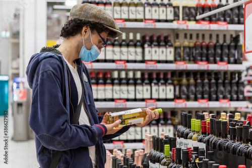 Leinwand Poster A young man in a medical mask chooses wine in a supermarket