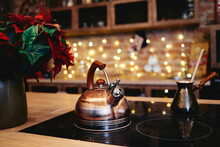 Christmas Flower And Metal Kettle On Table With Bokeh Lights On Background, Copy Space. Christmas Concept.