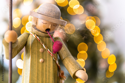 Fotografía Räuchermann mit Stock, rauchend mit Pfeife, steht vor Weihnachtsbaum mit unschar